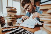 Writer Working On Laptop Sits With Stack Of Book. Portrait Of Handsome Caucasian Hardworking Caucasi poster