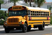 stock photo of bus driver  - yellow american school bus driving along the street - JPG