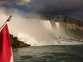 Majestic Falls In Niagara Falls . Gorgeous View Under A Blue Sky Canadian Flag Seen Next To Falls poster