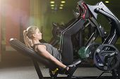 Sportive Woman Using Weights Press Machine For Legs. Gym. poster
