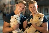Dogs Bring Them Joy. Muscular Men With Dog Pets. Happy Twins With Muscular Look. Spitz Dogs Love The poster