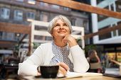 old age, leisure, retirement and people concept - happy senior woman with coffee and notebook dreami poster