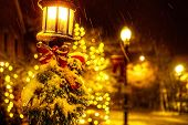 Christmas Tree Branches And A Red Bow On A Lantern Under A Falling Snow. Street Lamp With Christmas  poster