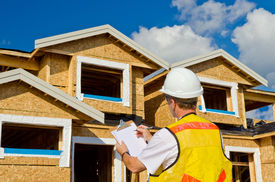 stock photo of 2x4  - A man in a hard hat standing in front of an house holding a clipboard in his hand - JPG