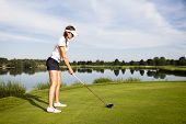 Girl golf player focusing on golf ball to tee off in tee-box.