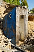 picture of outhouses  - Old weathered partially blue outhouse with crescent moons on each sidethe epitome of outhouses - JPG