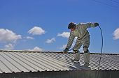 foto of roof-light  - A tradesman uses an airless spray to paint the roof of a building - JPG