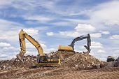 stock photo of earth-mover  - Two backhoes excavating at a construction site - JPG