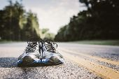 stock photo of shoe  - Lone pair of new running shoes just waiting to be used on an open road - JPG