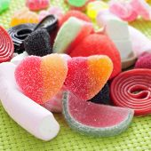 stock photo of gummy bear  - closeup of a pile of different candies on a green woven background - JPG