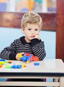 Portrait of bored little boy holding blocks sitting at desk in classroom