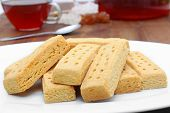 stock photo of shortbread  - tasty shortbread fingers with black tea on a wooden board - JPG