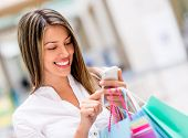 stock photo of hispanic  - Happy woman using cell phone at a shopping center - JPG