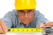 Closeup of a construction worker in hard hat using a measuring tape with the numbers facing forward.