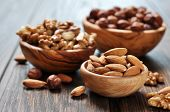 stock photo of hazelnut  - Almonds walnuts and hazelnuts in wooden bowls on wooden background - JPG