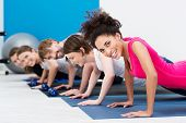 stock photo of vivacious  - Group of fit young people doing push ups while working out in a class in the gym with focus to a beautiful vivacious young African American woman in the foreground - JPG