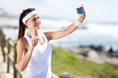 active young woman taking self portrait outdoors before exercise
