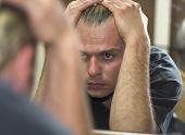 foto of sad man  - man looking at self reflection in mirror - JPG