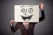 foto of faceless  - Young woman holding a cardboard with a smiley face on it in front of her head - JPG