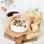 stock photo of brie cheese  - Baked Camembert cheese with thyme and toasted bread on wooden board - JPG