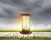 foto of hourglass figure  - Conceptual image with sandglass and silhouettes of business people around - JPG