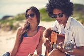 foto of serenade  - Cute hispanic couple playing guitar serenading on beach in love and embrace - JPG