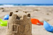 foto of shovel  - closeup of a sandcastle and some toy shovels on the sand of a beach - JPG