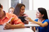 image of 13 year old  - Teacher Helping Female High School Student In Classroom - JPG