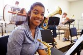 picture of orchestra  - Female Pupil Playing Saxophone In High School Orchestra - JPG