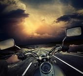 stock photo of storms  - Rider on the motorcycle moving towards dark storm clouds - JPG