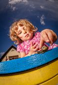 picture of creeping  - Little girl looking at the snail creeping on top of the sandpit - JPG