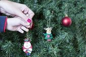 pic of rudolph  - closeup of hands of a son and a mum decorating the Christmas tree hanging an adornment of a Santa Claus - JPG
