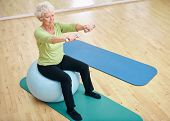 foto of dumbbell  - Senior female sitting on a fitness ball and lifting dumbbells - JPG