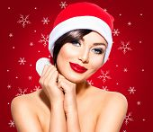 Постер, плакат: Christmas Woman Beauty Model Girl in Santa Hat over holiday red Background with snowflakes Holiday