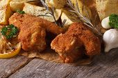 foto of southern fried chicken  - Fried chicken wings dipped in batter with potatoes close up on the table - JPG