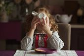 foto of girlie  - Little girl drinks tea from a large white cup