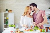 picture of amor  - Amorous young couple cooking in the kitchen - JPG