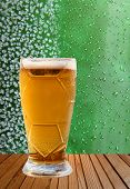 picture of ice crystal  - Beer glass taken closeup against of ice crystals and drips green background - JPG