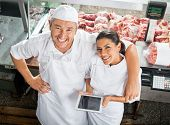 stock photo of slaughterhouse  - High angle portrait of happy male and female butchers with digital tablet in butchery - JPG