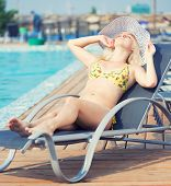 stock photo of sunbathers  - Young woman in bikini and hat in swimsuit laying on chaise - JPG