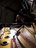 foto of grand piano  - Female pianist performing on a grand concert piano - JPG