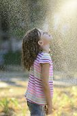 picture of dancing rain  - Happy little girl outdoor in a sunny day enjoying the light rain - JPG