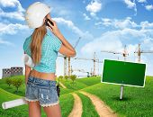 picture of country girl  - Beautiful girl builder in helmet holding paper scrolls and talking on phone - JPG