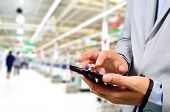 stock photo of supermarket  - Business Man using mobile phone while shopping in supermarket - JPG
