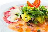 foto of rocket salad  - Isolated Mixed beef and salmon carpaccio served with salad rocket - JPG