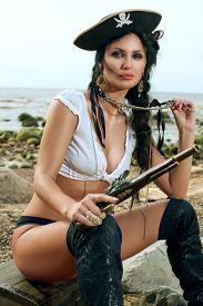 pic of pistols  - Beautiful pirate woman sitting on the beach with a classic pistol in her hand - JPG