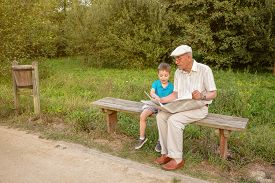 foto of sitting a bench  - Senior man and cute child reading a newspaper sitting on park bench - JPG