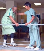 stock photo of physical therapist  - Young Philipino therapist help an older black man with his therapy - JPG