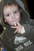 image of cigarette-smoking  - Little boy smoking a chocolate cigarette while looking at the camera - JPG