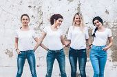 Group of four young diverse girls wearing blank white tshirt and jeans posing against rough street w poster